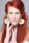 Rouquin belle fille avec des tranches de citron dans les oreilles — Photo