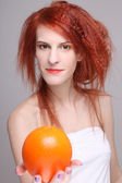 Portrait of redhaired girl with orange — Stock Photo