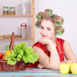Beautiful housewife with hair curlers in the kitchen — Stock Photo