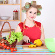 Young housewife cutting yellow pepper in the kitchen — Stock Photo
