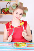 Attractive woman eating vegetables in the kitchen — Stok fotoğraf