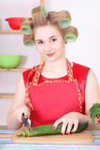 Attractive housewife cutting cucumber in the kitchen — 图库照片