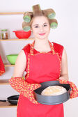 Young housewife with bread in the kitchen — Stock Photo