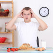 Shocked man sitting in the kitchen — Stock Photo