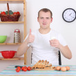 Young man having breakfast in the kitchen — Stock Photo
