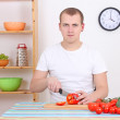 Man cutting red pepper in the kitchen — Stock Photo