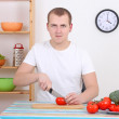 Man cutting tomato in the kitchen — Stock Photo