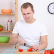 Husband cutting tomato in the kitchen — Stock Photo