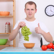 Young man with grape in the kitchen — Stock Photo