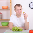Young man with green grape in the kitchen — Stock Photo