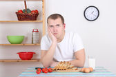 Sad man sitting in the kitchen — Stock Photo