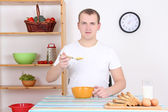 Man eating corn flakes with milk in the kitchen — Stockfoto