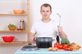 Attractive man cooking in the kitchen — Stock Photo