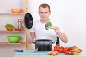 Young man cooking soup in the kitchen — Stock Photo