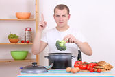Young man cooking broccoli in the kitchen — Stock Photo