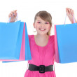 Portrait of happy teenage girl in pink with shopping bags — Stock Photo