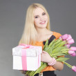 Portrait of beautiful blondie girl with gift and tulips — Stock Photo