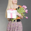 Portrait of beautiful blondie girl with gift and flowers — Stock Photo #21246941