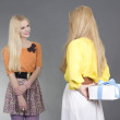 Young woman giving a present to her friend over grey — Stock Photo