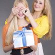 Young attractive woman giving a present to her surprised friend — Stock Photo
