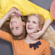 Stock Photo: Smiling teenage girls lying with colorful balloons