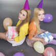 Smiling teenage girls with gifts and colorful balloons  — Stock Photo