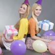 Smiling teenage girls sitting with gifts and colorful balloons  — Stock Photo
