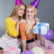 Teenage girls sitting with gifts and colorful balloons  — Stock Photo