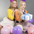 Girls sitting with gifts and colorful balloons  — Stock Photo