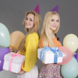 Girls with gifts and balloons at a birthday party — Stock Photo