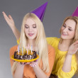 Teenage girls with birthday cake over grey — Stock Photo