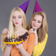 Two beautiful teenage girls with birthday cake — Stock Photo