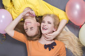 Smiling teenage girls lying with colorful balloons — Stock Photo