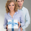 Young attractive couple with present — Stock Photo