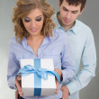 Young attractive couple with gift — Stock Photo