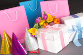 Tulips, gift boxes and birtday hats over grey — Stockfoto