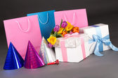 Composition of colorful tulips, gift boxes and birtday hats over — Stock Photo