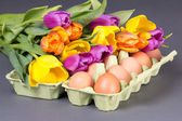 Bouquet of tulip flowers and eggs on grey — Stock Photo