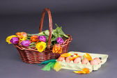 Brown basket with colorful tulips and eggs over grey — Stock Photo