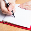 Hand writing in red notebook — Stock Photo
