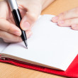 Stock Photo: Hand of young woman taking notes