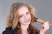 Portrait of young beautiful woman with make up brushes — Stock Photo