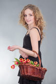 Young woman with basket of flowers — Stok fotoğraf