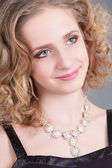 Close up portrait of young curly woman with necklace — Stock Photo