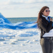 Portrait of young woman with scarf on winter beach — Stock Photo