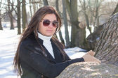 Portrait of young attractive woman with sunglasses in park — Stock Photo