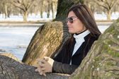 Young attractive woman with sunglasses in park — Stock Photo