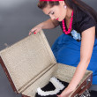 Young beautiful pinup girl packing retro suitcase — Stock Photo