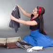 Beautiful pinup girl packing retro suitcase — Stock Photo
