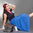 Funny pinup girl sitting on overfilled suitcase — Stock Photo